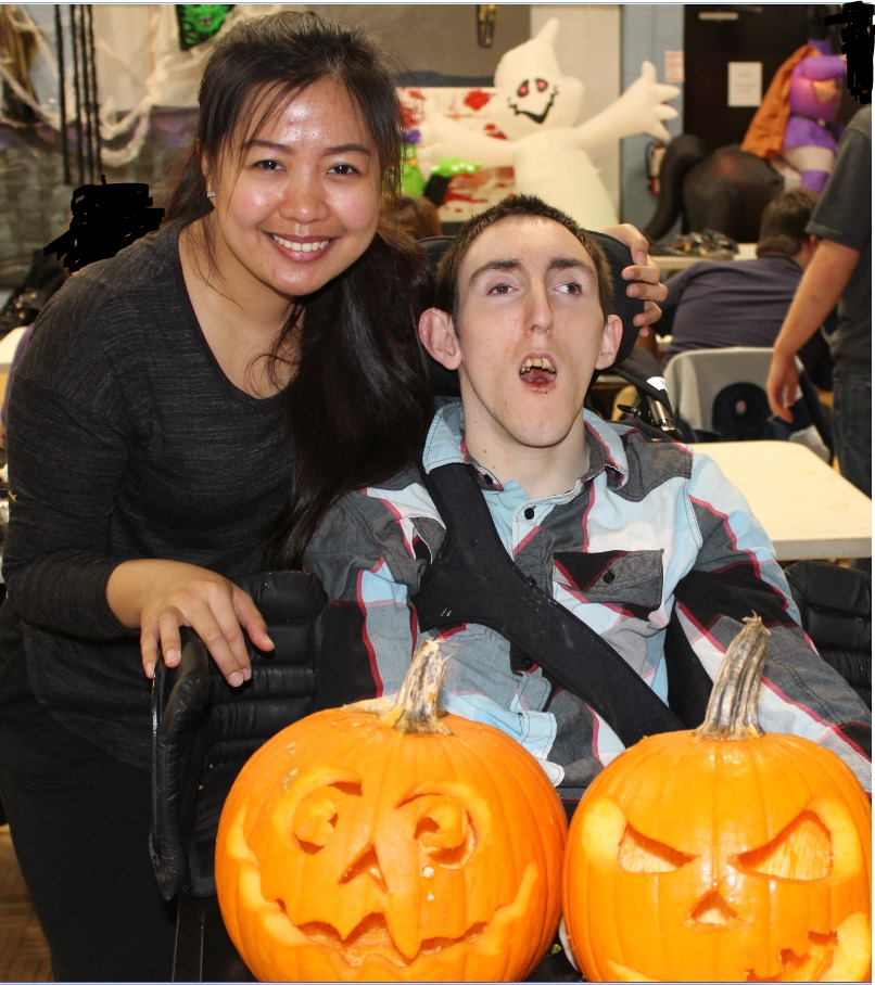 Image of Sunbeam person and person served behind two carved pumpkins