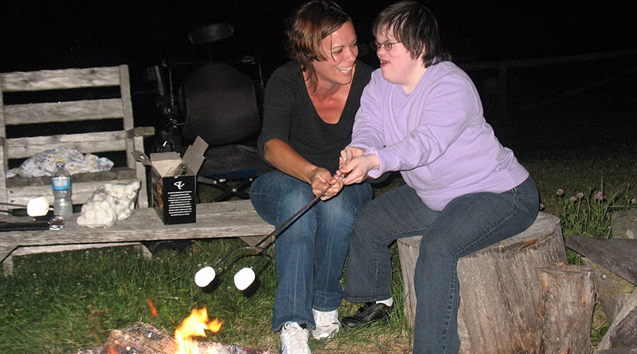 Photo of two people roasting marshmallows